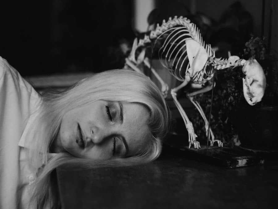 donna dorme di fianco allo scheletro di un dinosauro