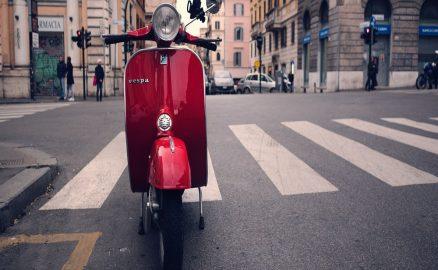 Vespa rossa parcheggiata in una strada italiana
