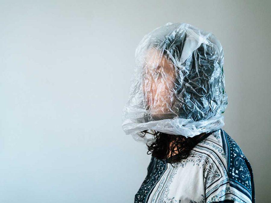 Donna con la testa nella busta di plastica