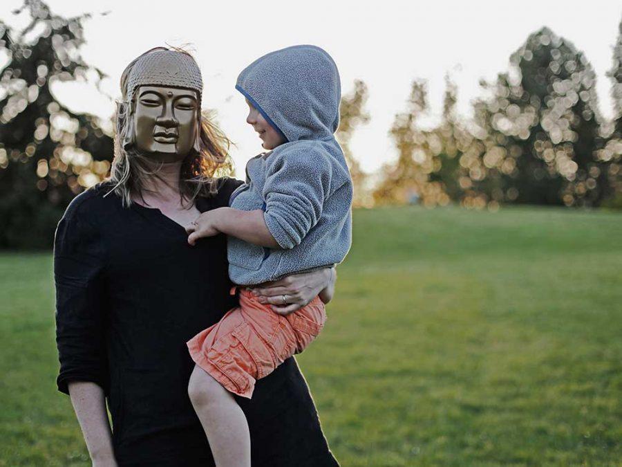 Mamma con maschera e bambino in braccio