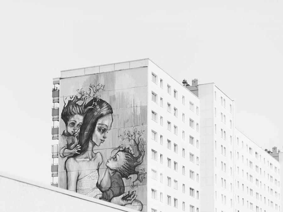 Murales con disegno di una mamma con in braccio i figli