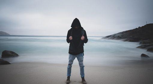 Ragazzo in spiaggia dà le spalle al mare