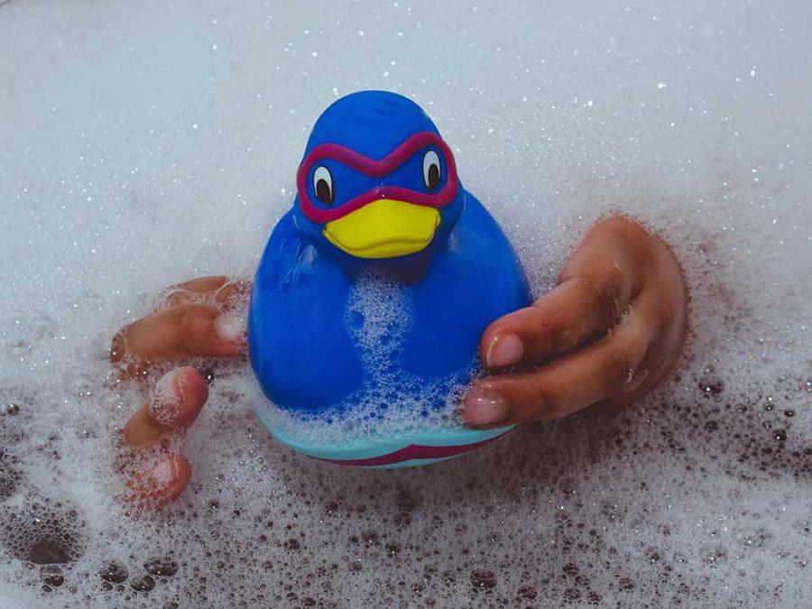 Vasca piena di acqua e schiuma con paperella blu
