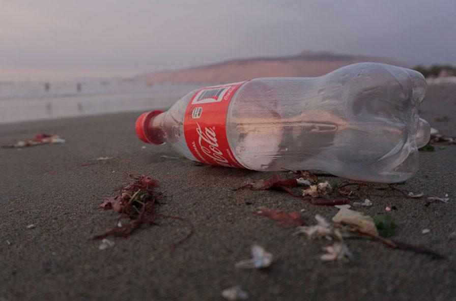 Bottiglia di plastica abbandonata in spiaggia